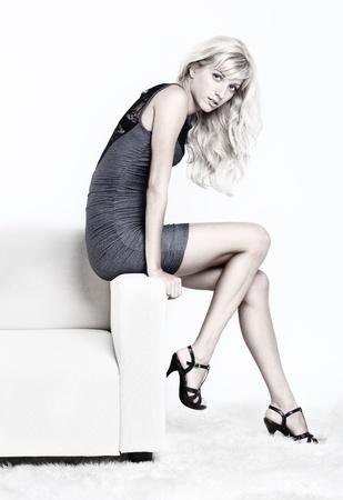 modellini: Full-length ritratto di bella giovane donna bionda sul divano con pellicce bianche al piano