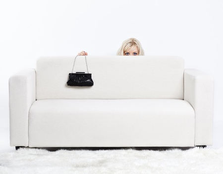 full-length portrait of beautiful young blond woman on couch with white furs on floor photo