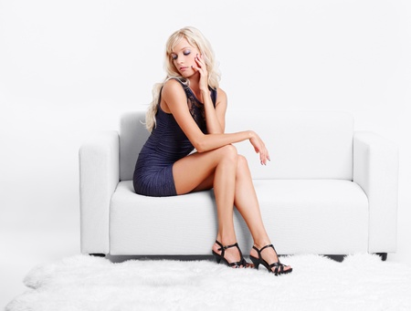 full-length portrait of beautiful young blond woman on couch with white furs on floor Stock Photo - 10421709