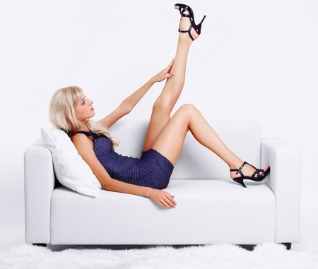full-length portrait of beautiful young blond woman on couch streching legs in court shoes photo
