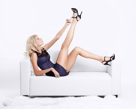 court shoes: full-length portrait of beautiful young blond woman on couch streching legs in court shoes