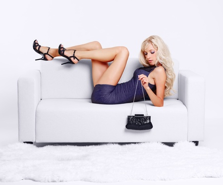 full-length portrait of beautiful young blond woman with hand bag lying on couch with white furs on floor Stock Photo - 10421695