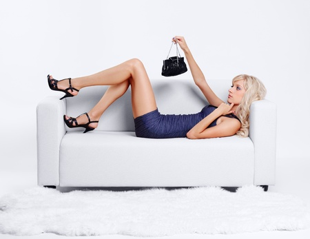 full-length portrait of beautiful young blond woman with hand bag lying on couch with white furs on floor photo