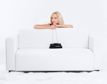 handbag model: full-length portrait of beautiful young blond woman on couch with white furs on floor