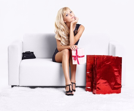 handbag model: full-length portrait of beautiful young blond woman on couch with shopping bags and gift in hands