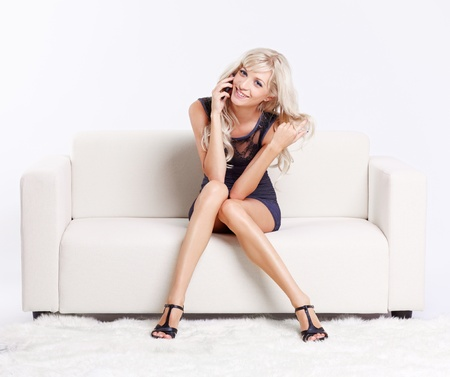 attractive couch: full-length portrait of beautiful young blond woman on couch speaking over her mobile phone