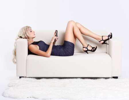 full-length portrait of beautiful young blond woman relaxing on couch with smartphone Stock Photo