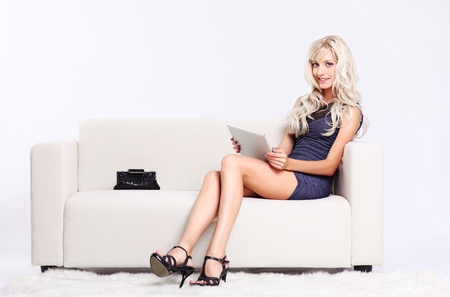 full-length portrait of beautiful young blond woman on couch with tablet pc photo