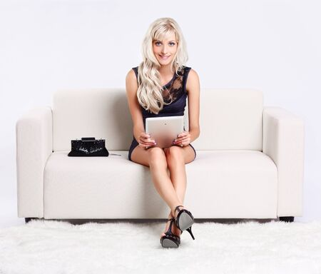 full-length portrait of beautiful young blond woman on couch with tablet pc Stock Photo - 10421720