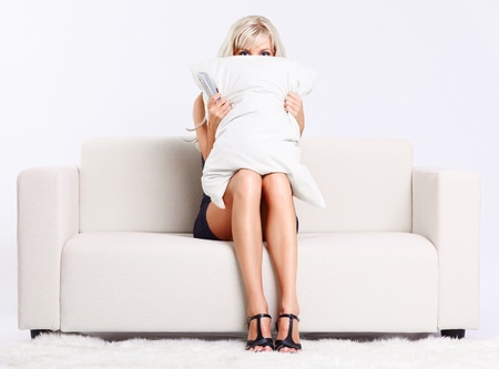 beauty model: full-length portrait of beautiful young blond woman sitting on couch with remote control watching scary movie and hiding behind the pillow