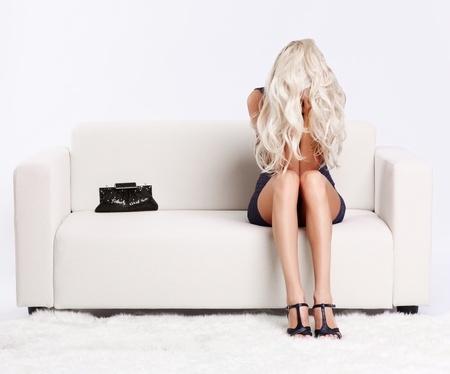 full-length portrait of depressed beautiful young blond woman sitting on couch and hiding her face in hands and hair photo