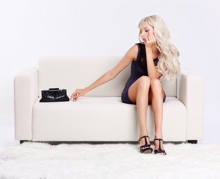 full-length portrait of beautiful young blond woman on couch with white furs on floor Stock Photo - 10421691