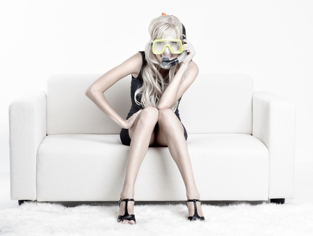 young blond woman in scuba mask on couch with white furs on floor photo