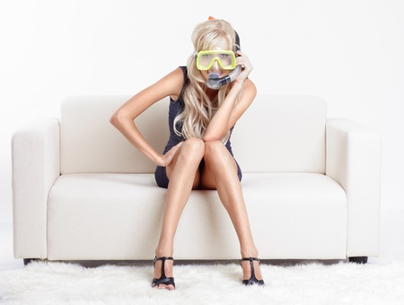 young blond woman in scuba mask on couch with white furs on floor Stock Photo - 10421741
