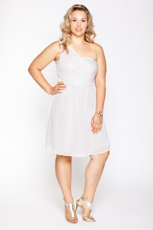 large woman: full-length portrait of beautiful plus size curly young blond woman posing on gray in white dress and court shoes Stock Photo