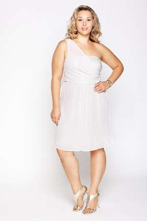 shoes model: full-length portrait of beautiful plus size curly young blond woman posing on gray in white dress and court shoes Stock Photo
