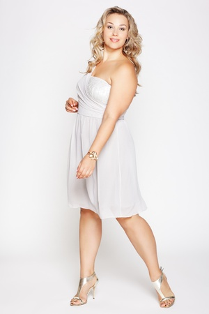 curvy: full-length portrait of beautiful plus size curly young blond woman posing on gray in white dress and court shoes Stock Photo