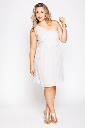 size: full-length portrait of beautiful plus size curly young blond woman posing on gray in white dress and court shoes Stock Photo