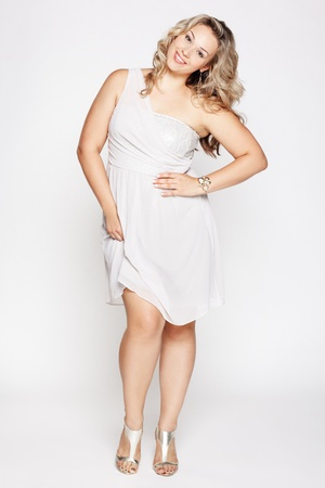 plus size: full-length portrait of beautiful plus size curly young blond woman posing on gray in white dress and court shoes Stock Photo