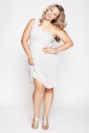 cerveza negra: LP retrato de hermosa plus tamaño rizado joven mujer rubia posando en gris en zapatos de vestir y corte blancos