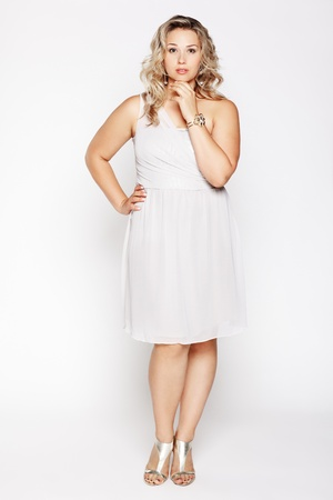 plus size woman: full-length portrait of beautiful plus size curly young blond woman posing on gray in white dress and court shoes Stock Photo