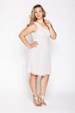 court shoes: full-length portrait of beautiful plus size curly young blond woman posing on gray in white dress and court shoes Stock Photo
