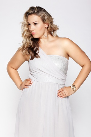 plus size: portrait of beautiful plus size curly young blond woman posing on gray Stock Photo