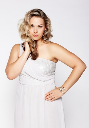 size: portrait of beautiful plus size curly young blond woman posing on gray Stock Photo