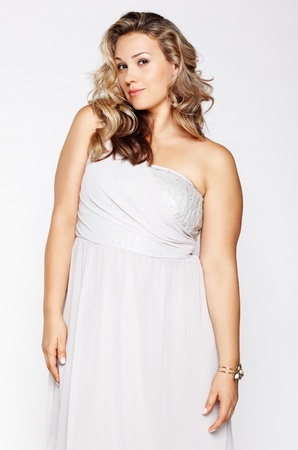 curvy woman: portrait of beautiful plus size curly young blond woman posing on gray Stock Photo