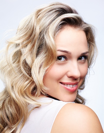 portrait of beautiful plus size curly young blond woman posing on gray Stock Photo