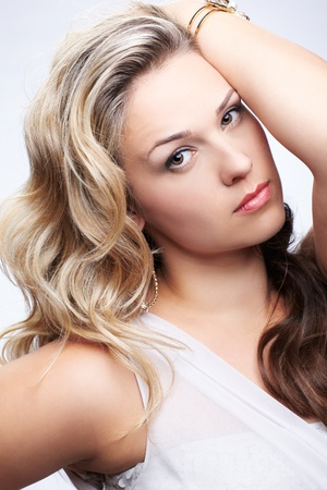 portrait of beautiful plus size curly young blond woman posing on gray photo