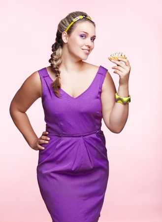 large size: portrait of beautiful plus size curly young blond woman posing on pink with sweet pastry