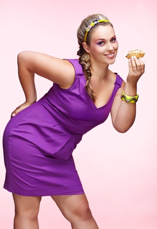 plus size: portrait of beautiful plus size curly young blond woman posing on pink with sweet pastry