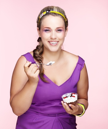 portrait of beautiful plus size curly young blond woman posing on pink with sweet pastry