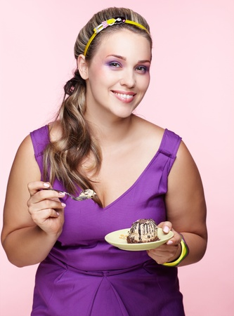 portrait of beautiful plus size curly young blond woman posing on pink with sweet pastry photo