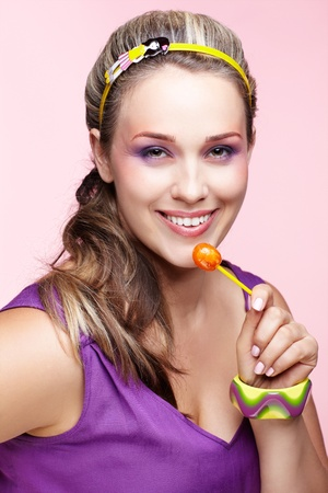 portrait of beautiful plus size curly young blond woman posing on pink with lollipop photo