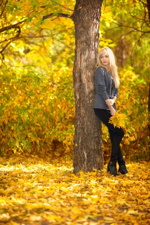 Autumn woman under tree in park with fall leaves photo