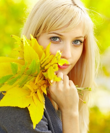 Autumn woman with yellow fall maple leaves photo