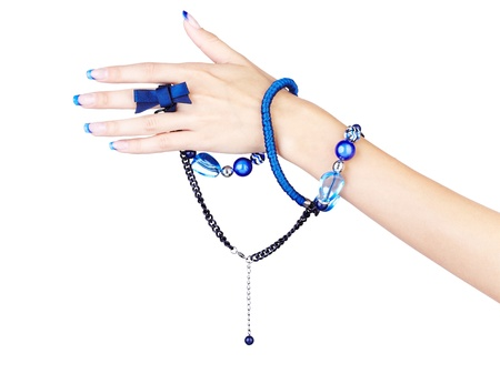 bead jewelry: isolated body part shot of beautiful young womans manicured hands with fancy blue beads on white