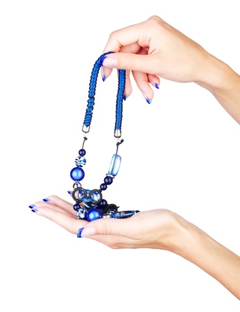 naildesign: isolated body part shot of beautiful young womans manicured hands with fancy blue beads on white