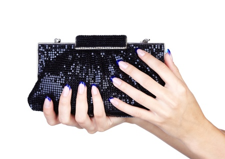closeup on bags: isolated body part shot of beautiful young womans manicured hands with fancy clutch on white Stock Photo