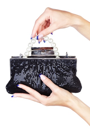 isolated body part shot of womans manicured hands holding fancy clutch with pearl beads inside photo