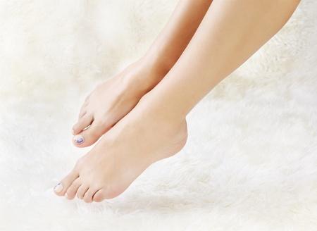 jolie pieds: tir la partie du corps des jambes belle femme jeune en bonne santé sur la fourrure blanche