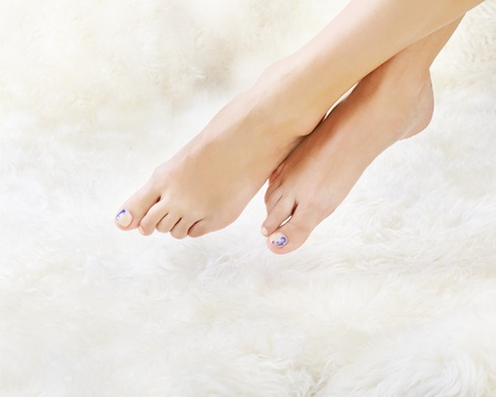 body part shot of beautiful healthy young womans legs on white fur Stock Photo