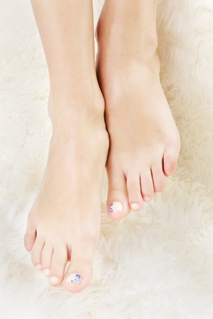 beautiful ankles: body part shot of beautiful healthy young womans legs on white fur Stock Photo