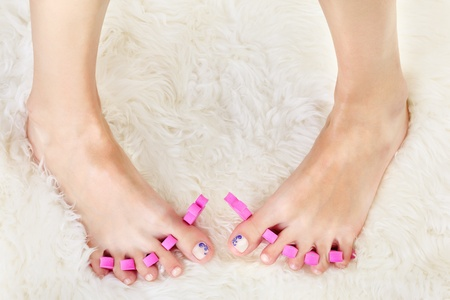 young girl feet: body part shot of beautiful healthy young womans feet in pedicure toe separators on white fur