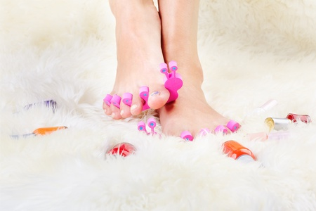 foot model: body part shot of healthy womans feet in pedicure toe separators with vials of nail olish around Stock Photo
