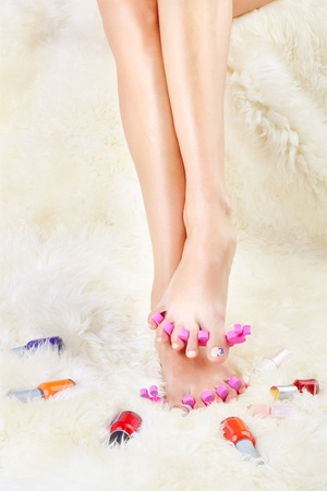 body part shot of healthy womans feet in pedicure toe separators with vials of nail olish around photo