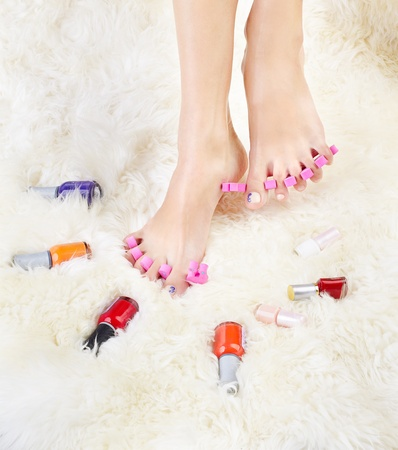 separators: body part shot of healthy womans feet in pedicure toe separators with vials of nail olish around Stock Photo