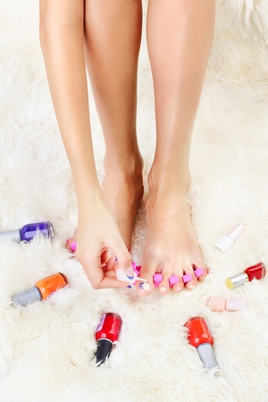 separators: body part shot of healthy womans feet in pedicure toe separators. hand is putting polish on toenail Stock Photo